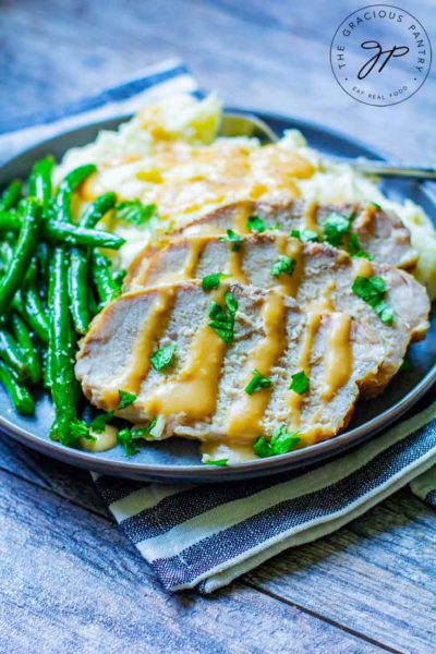 Three slices of this Slow Cooker Pork Loin is sliced and placed on a plate next to mashed potatoes and green beans. Gravy dresses the pork and potatoes.
