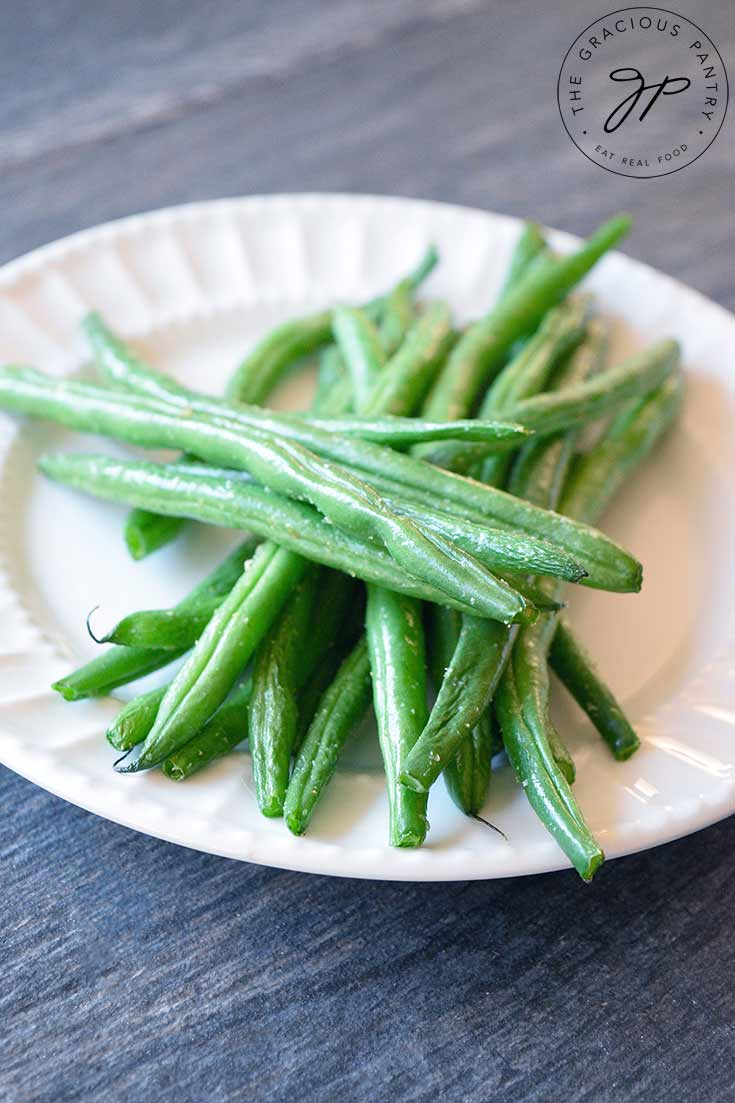 A single, white plate sits piled high with bright green, Air Fryer Green Beans.