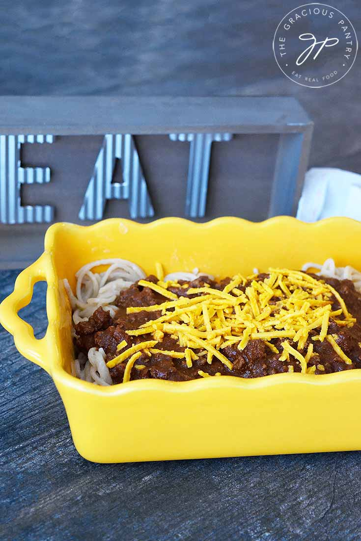 "A yellow casserole dish filled with Cincinnati chili covered pasta, sits next to a wooden sign that says, ""eat""."