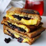 A Grilled Cheese Sandwich With Blackberries sits with a glass of juice behind it, ready to enjoy for lunch.