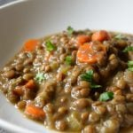 A white bowl sits on a table with a nice helping of this Vegan Instant Pot Lentil Soup. You can see carrot slices in with the lentils and fresh herbs sprinkled over the top.
