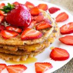 A stack of spelt pancakes sits on a white plate, topped with fresh strawberries and maple syrup.