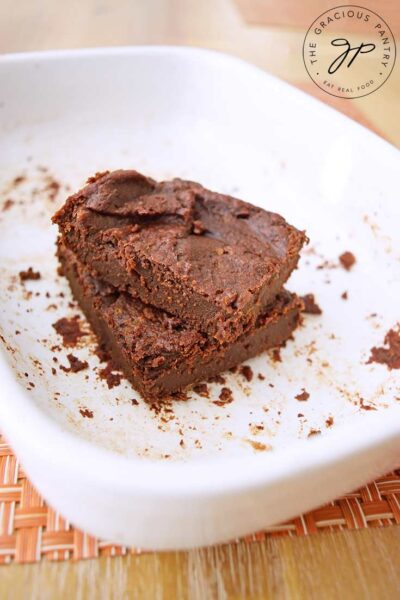 Two of these Flourless Brownies sit stacked in their baking dish.