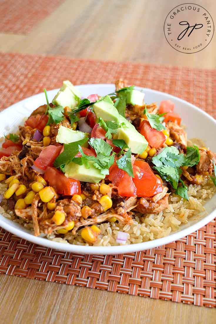 Instant Pot Mexican Chicken sits in a white bowl, garnished with toppings and ready to eat.