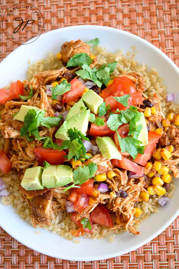 An overhead view of this Instant Pot Mexican Chicken shows a delicious view of mostly the garnishings with little bits of chicken and brown rice showing around the edges.