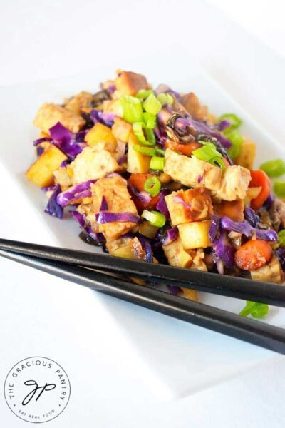 A side view of this Japanese Tempeh Skillet shows the tempeh , carrots, purple cabbage and green onions if bright, vibrant colors against a white plate.