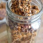 A canning jar sits filled with this Pumpkin Spice Granola Bark. The lid is off so you can see the bark inside the jar from the top as well as the sides.