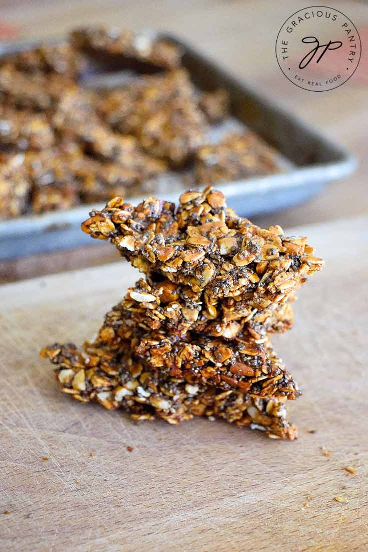 A stack of thisPumpkin Spice Granola Bark sits on a cutting board with the baking pan sitting behind it.