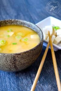 A delicious bowl of miso soup sits next to a smaller bowl of tofu with sliced green onions on top.
