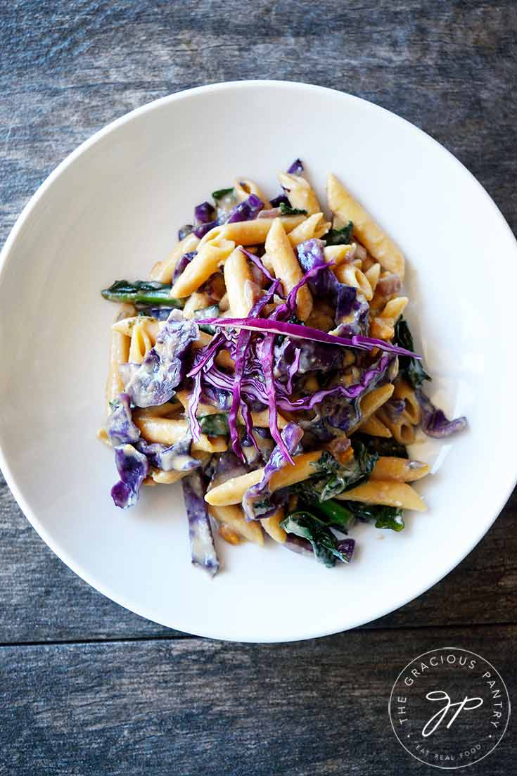 This Red Cabbage Pasta sits in a white bowl and the view is from overhead. You can see lots of red cabbage and bits of green kale mixed into the noodles.