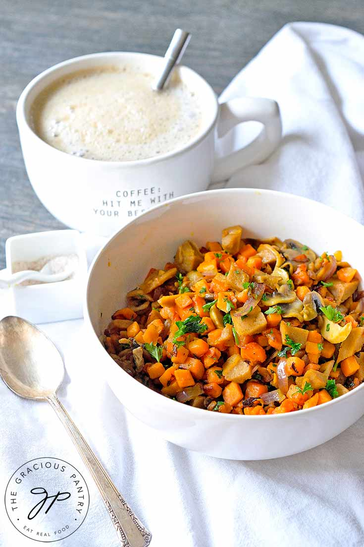 This Sweet Potato Breakfast Scramble With Seitan, sits in a white bowl, ready to eat. A cup of coffee sits next to it.