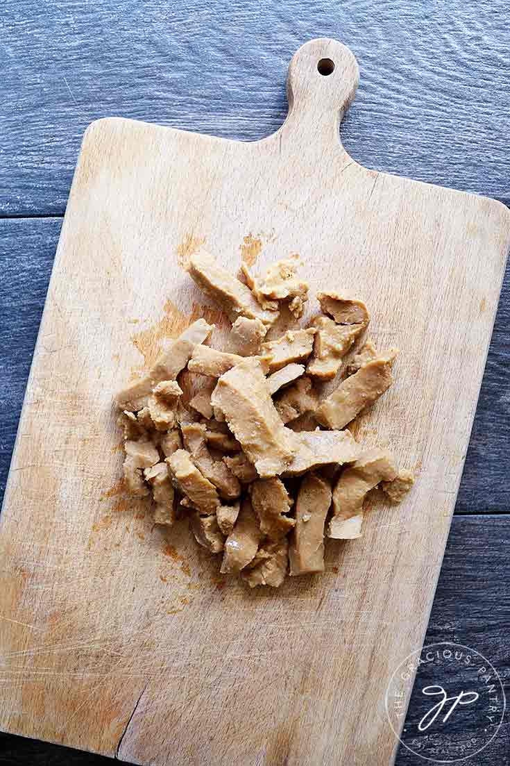This image, shows pieces of Seitan on a wooden cutting board.