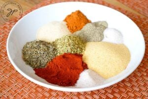 Individual spices sit next to each other in a bowl, just prior to mixing.