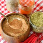 A wooden bowl filled with this Cajun Seasoning Recipe, sits with a serving spoon in the bowl and jars of spices and measuring spoons around it.