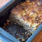 The cooked ground turkey meatloaf sits partially cut in the loaf pan. A piece of the meatloaf has been removed.