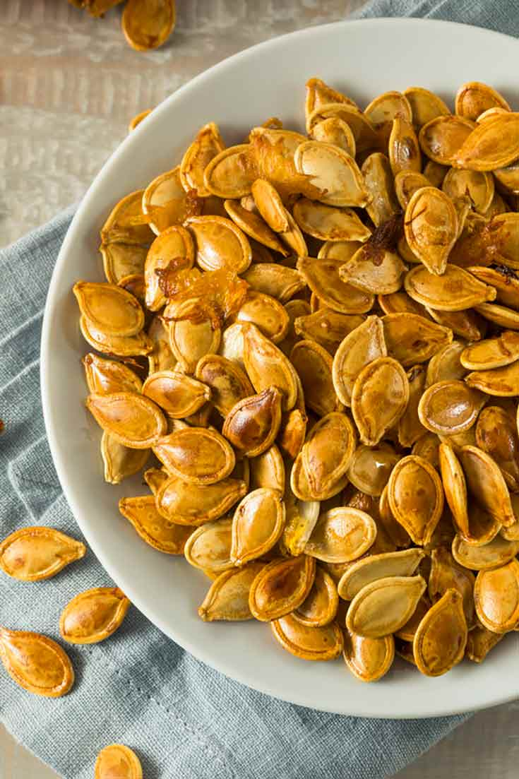 A bowl of roasted pumpkin seeds sits on a table. The seeds are golden brown. One of many Pumpkin Seed Recipes in this blog post.