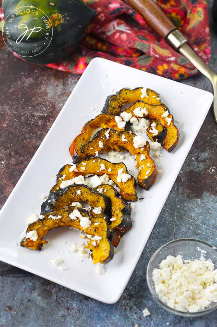 A platter of this Roasted Acorn Squash With Feta sits on a table with a bowl of feta crumbles next to it, all ready to serve.