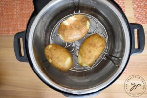 Step three is to place your potatoes on the trivet.
