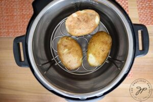 Step four for making these Instant Pot Baked Potatoes is to add water to the IP insert.