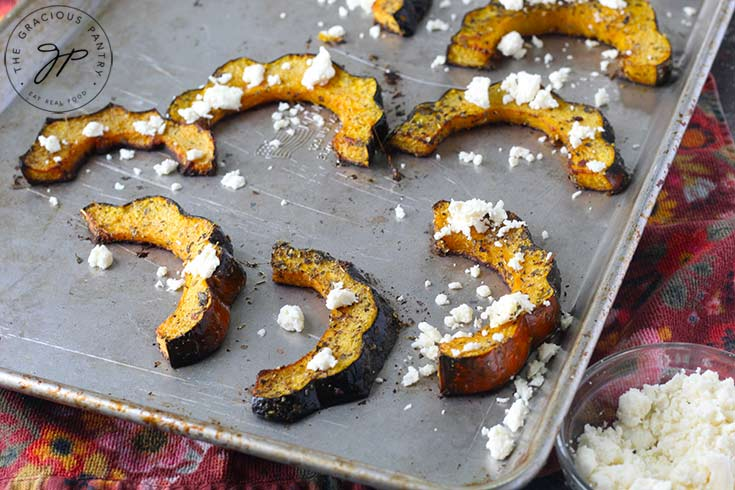 Step nine of this Roasted Acorn Squash recipe is to sprinkle the squash with feta cheese crumbles.