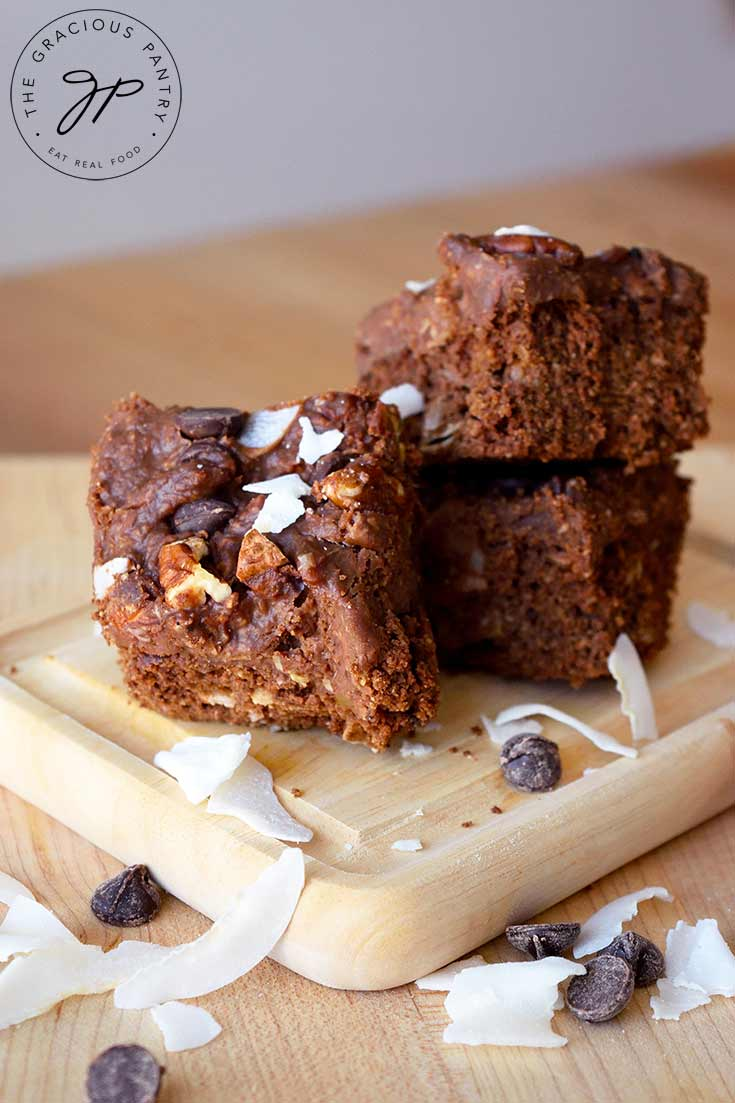 A stack of German Chocolate Brownies sits on a cutting board with coconut flakes and chocolate chips strewn around the board.