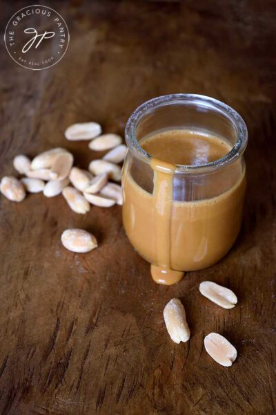 A jar of this peanut sauce sits with a drip coming down the side of the jar onto the table. A few peanuts are scattered around the jar.