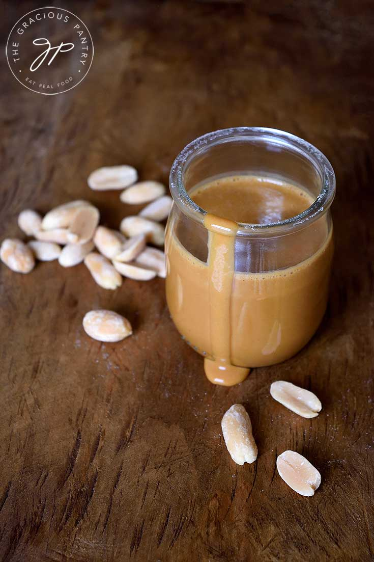 A jar of this sauce sits with a drip coming down the side of the jar onto the table. A few peanuts are scattered around the jar. Learn how to make peanut sauce with this vegan peanut sauce recipe. It's the perfect multipurpose condiment! Great as a dip, salad dressing, or stir fry sauce.