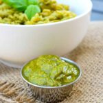 A small container of this Vegan Pesto Recipe With Basil And Cashews sits in front of a bowl of pesto pasta on a table.