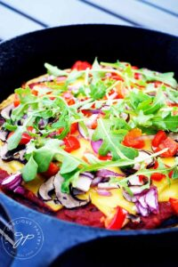 A black skillet sits with this Vegan Pizza Dough and finished toppings.