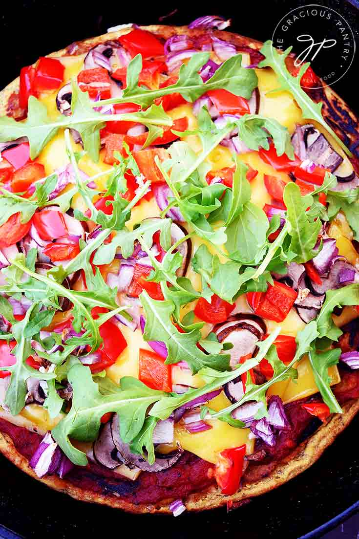 An overhead view of this Vegan Pizza Dough with all it's toppings. You can see arugula, red peppers, purple onions and the creamy yellow of the vegan cheese.