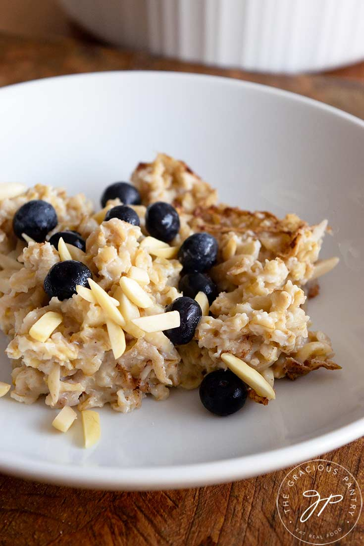 A portion of baked oatmeal sits in a white bowl, topped with fresh blueberries.