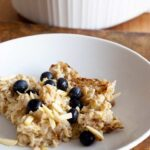 Baked Oatmeal Recipe served at the table in white dishes. Fresh blueberries garnish the oatmeal.