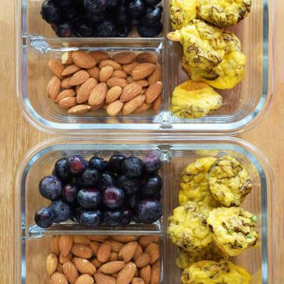 Two containers filled with mini egg muffins, blueberries and raw almonds sit next to each other, ready to go into the fridge for busy mornings. This is part of the Eggs and Oats Meal prep Plan