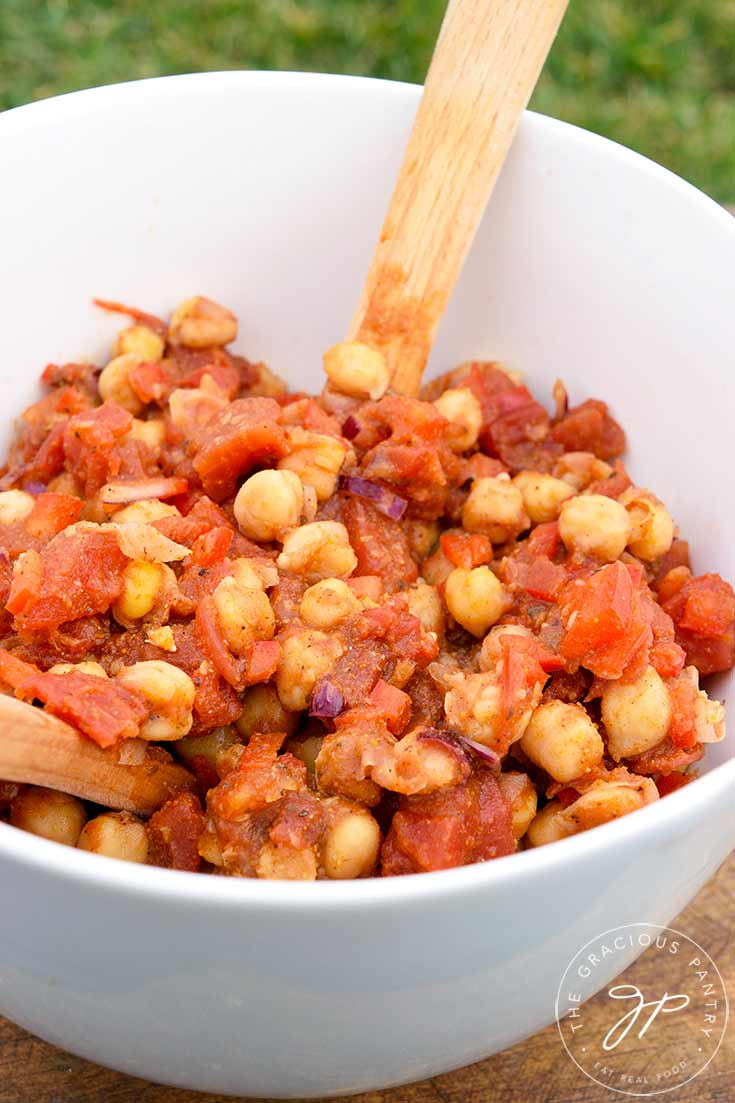 A white serving bowl with a wooden spoon sits filled with this Indian Chickpea Salad, ready to serve.