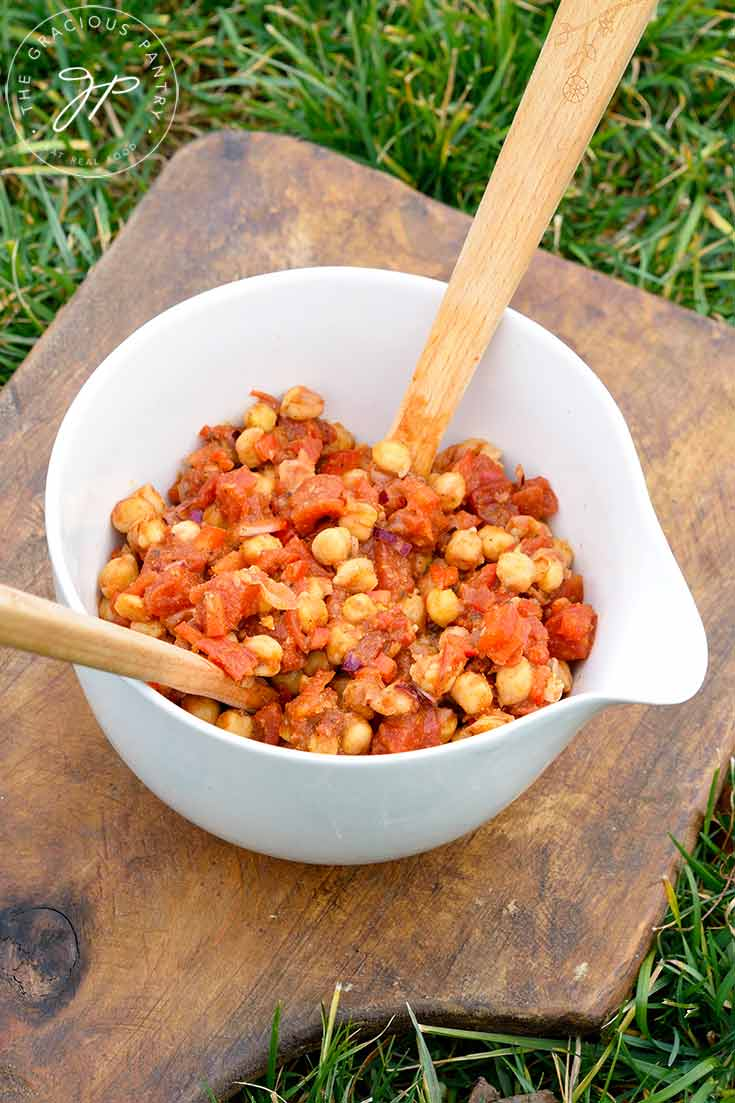 A further back view of this Indian Chickpea Salad shows two wooden serving spoons in the bean salad, ready to serve up a dish of this deliciousness.
