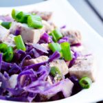 A white bowl sits on a table filled with purple cabbage, green onions and chunks of tofu in this Tofu Stir Fry Recipe.