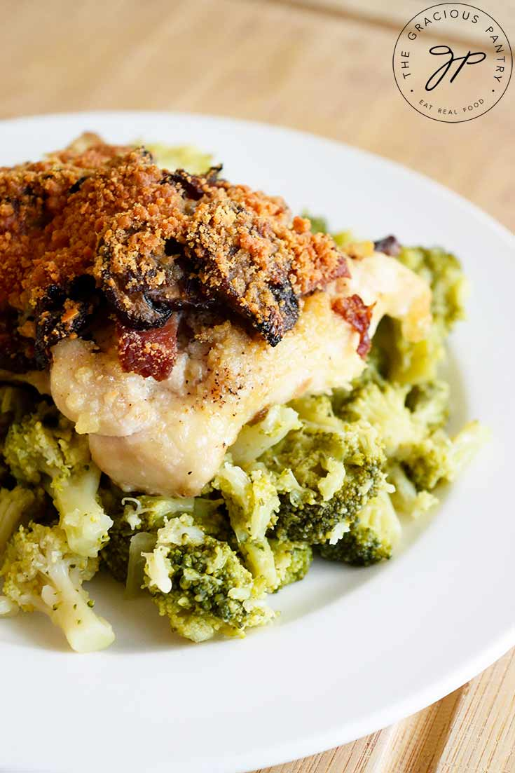 A Bacon Stuffed Chicken Thigh sits on a base of broccoli on a white plate. Just one idea for serving this deliciousness.