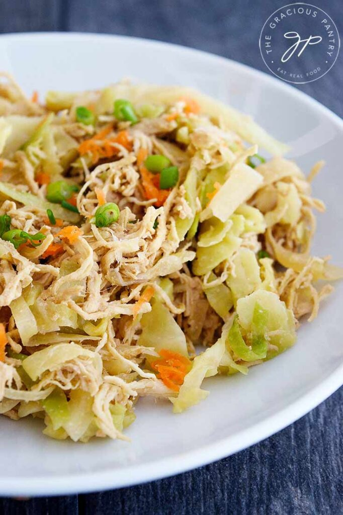 A white bowl filled with this Egg Roll In A Bowl Recipe sits on a slate tabletop. You can see bits of chicken, cabbage, shredded carrots and sliced green onions.