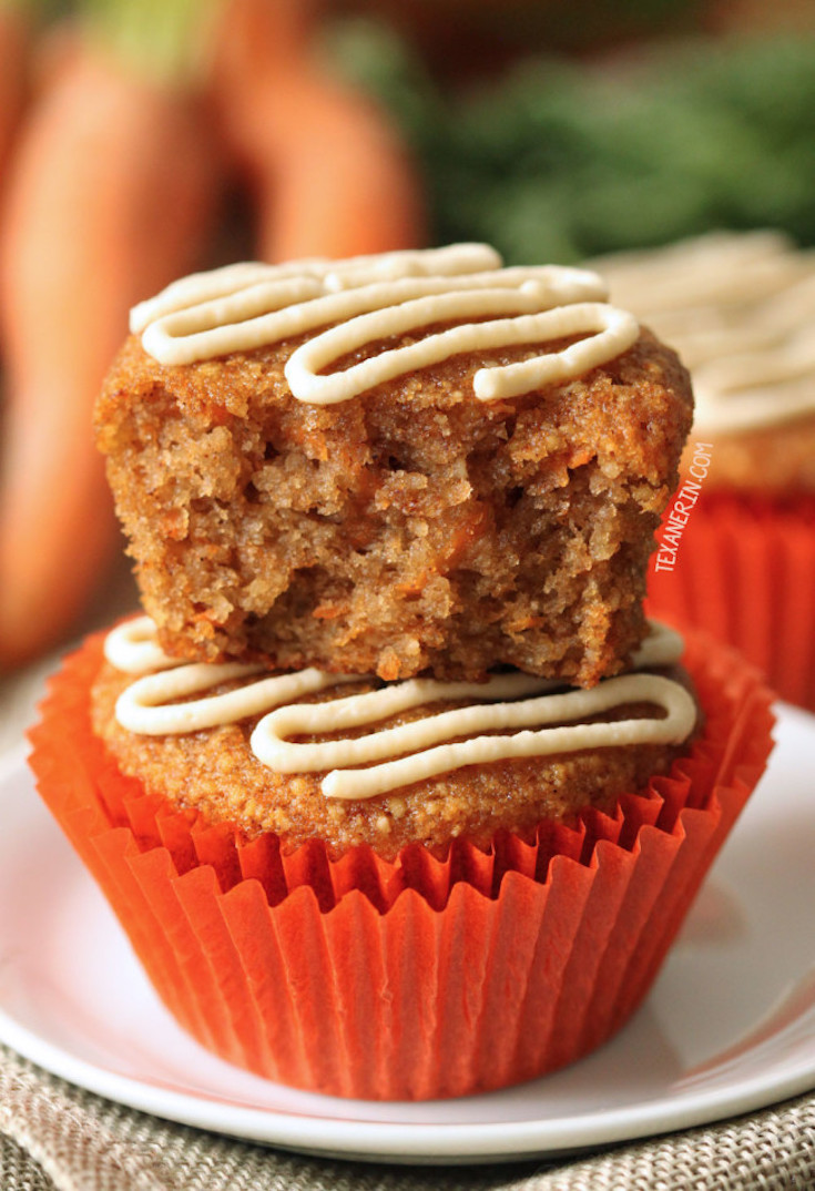 A close up of two healthier carrot cake muffins stacked on top of each other. A bite has been taken from the muffin on top.