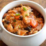 A delicious bowl of this Chicken Stew Recipe sits warm and inviting. You can see bits of black beans and carrots amidst the chicken and red sauce.