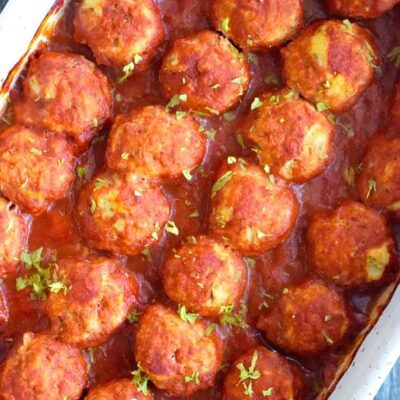 An overhead view looking down into a white casserole dish filled with this freshly made Italian Meatballs.