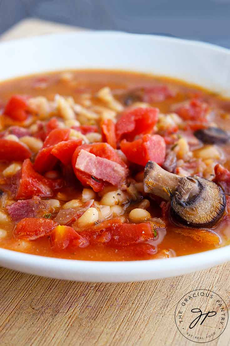 ThisItalian Navy Bean Soup fills a white bowl. You can see bits of bacon, mushrooms, tomatoes and plenty of navy beans sitting in a delicious broth.