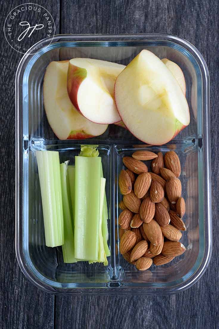 A prep container filled with apples, celery and almonds.