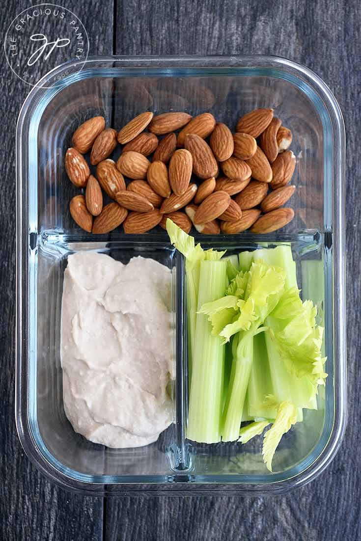 A meal prep container with almonds, celery and hummus.