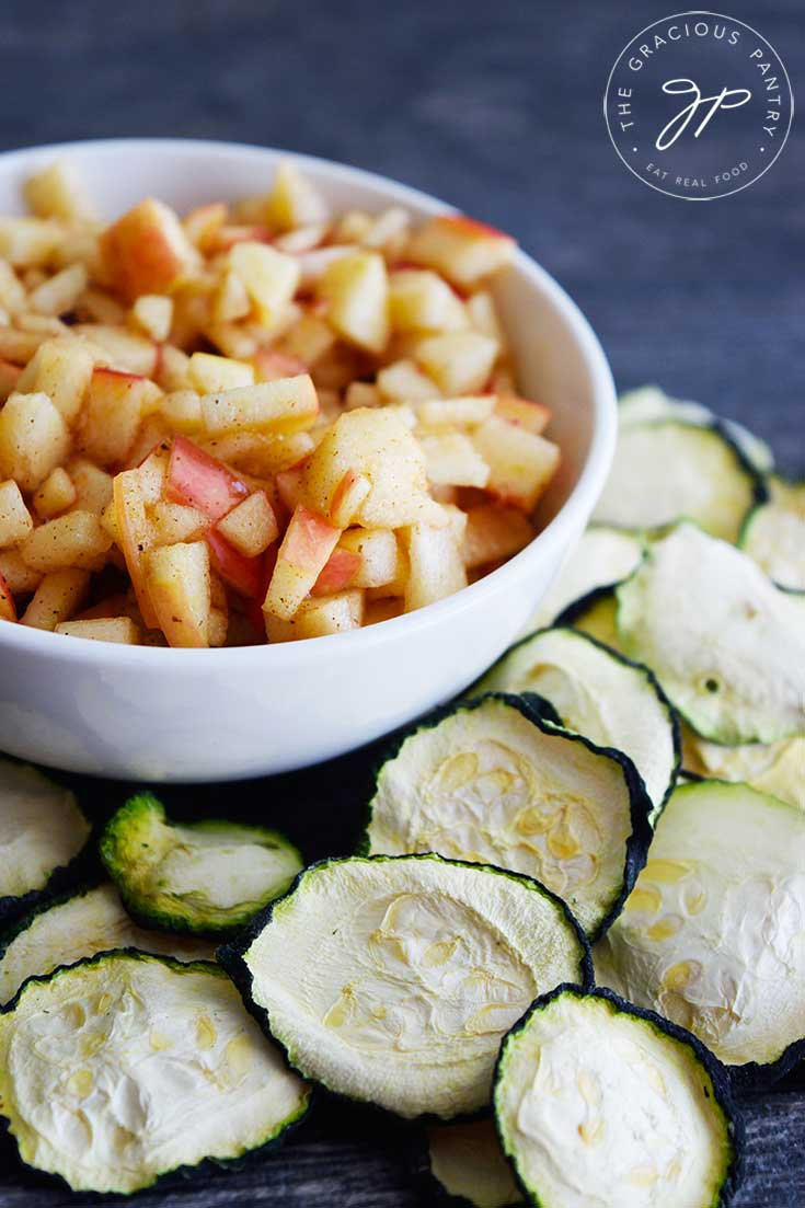 A small bowl of apple salsa sits surrounded by dehydrated zucchini chips. A tasty snack!
