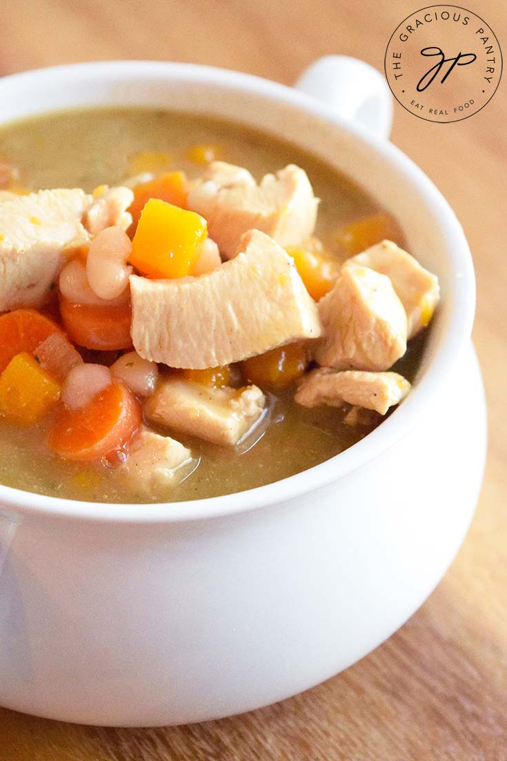 A white bowl filled with this Chicken Stew Recipe With Butternut Squash. You can see the chicken, carrots and bits of butternut squash sitting in a thickened broth.