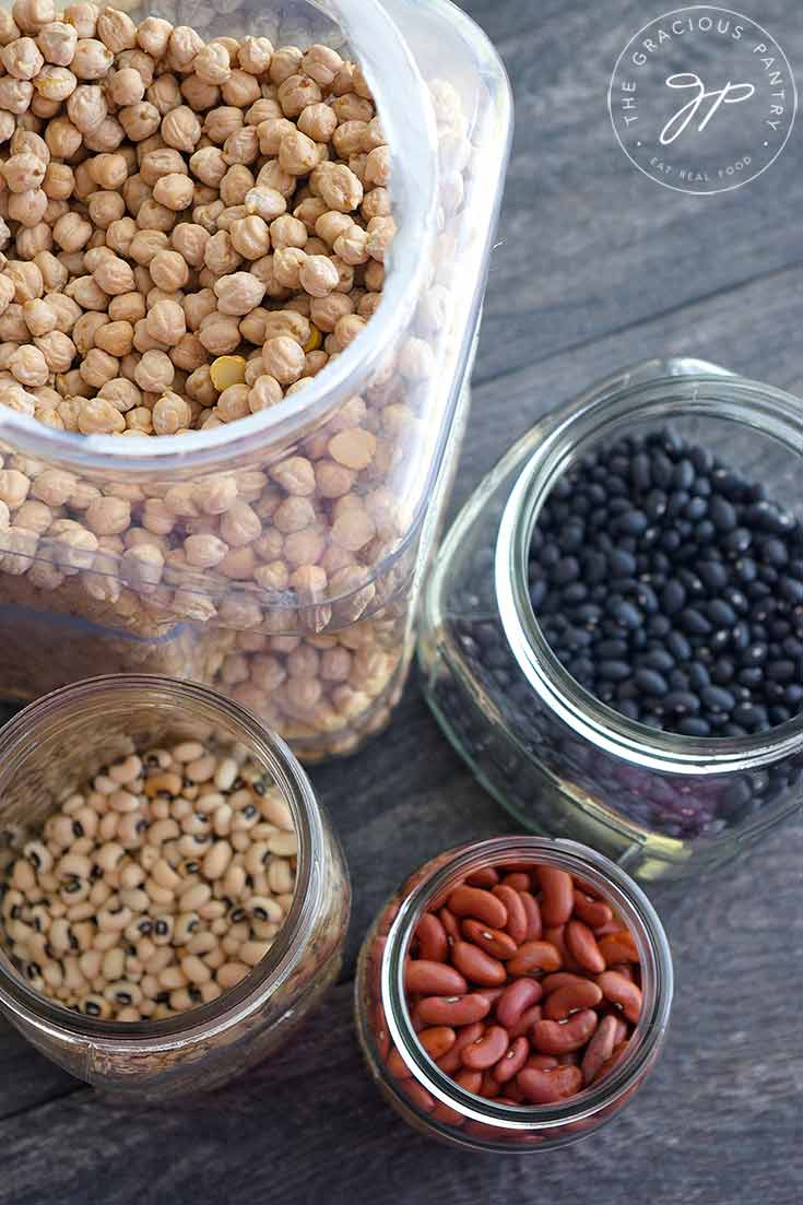 Containers of various beans sit with their lids off so you can see the beans in this guide to How To Cook Dry Beans.