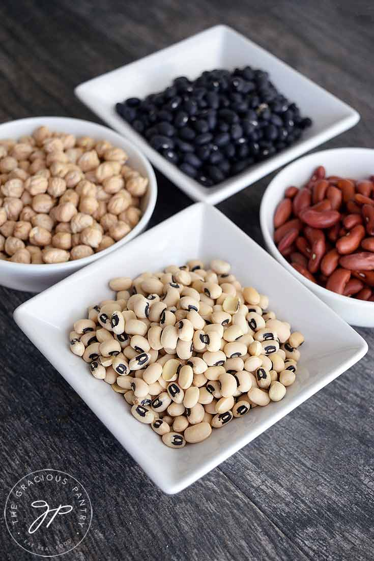 Four bowls sit with four different kinds of dry beans in them.