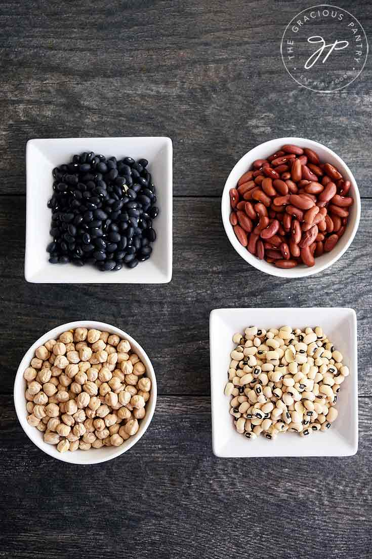 An overhead view of four different types of beans in separate, white bowls in this guide to How To Cook Dry Beans.