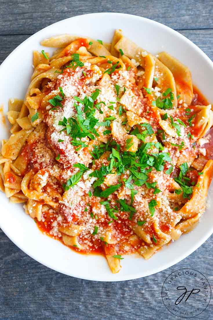 An overhead view of a freshly made bowl of pasta with red sauce and garnished with chopped herbs and parmesan cheese. Read more in this guide to How To Make Homemade Pasta.